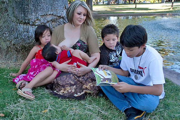 Mother breastfeeding baby at a park with her children